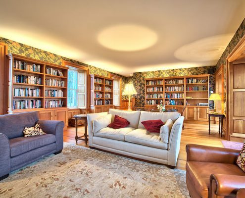 Soft comfortable seating by open fire in library